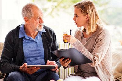 adult woman reminding senior man abuot medicine
