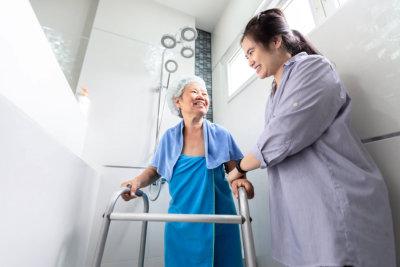 caregiver assisting senior woman in bathroom